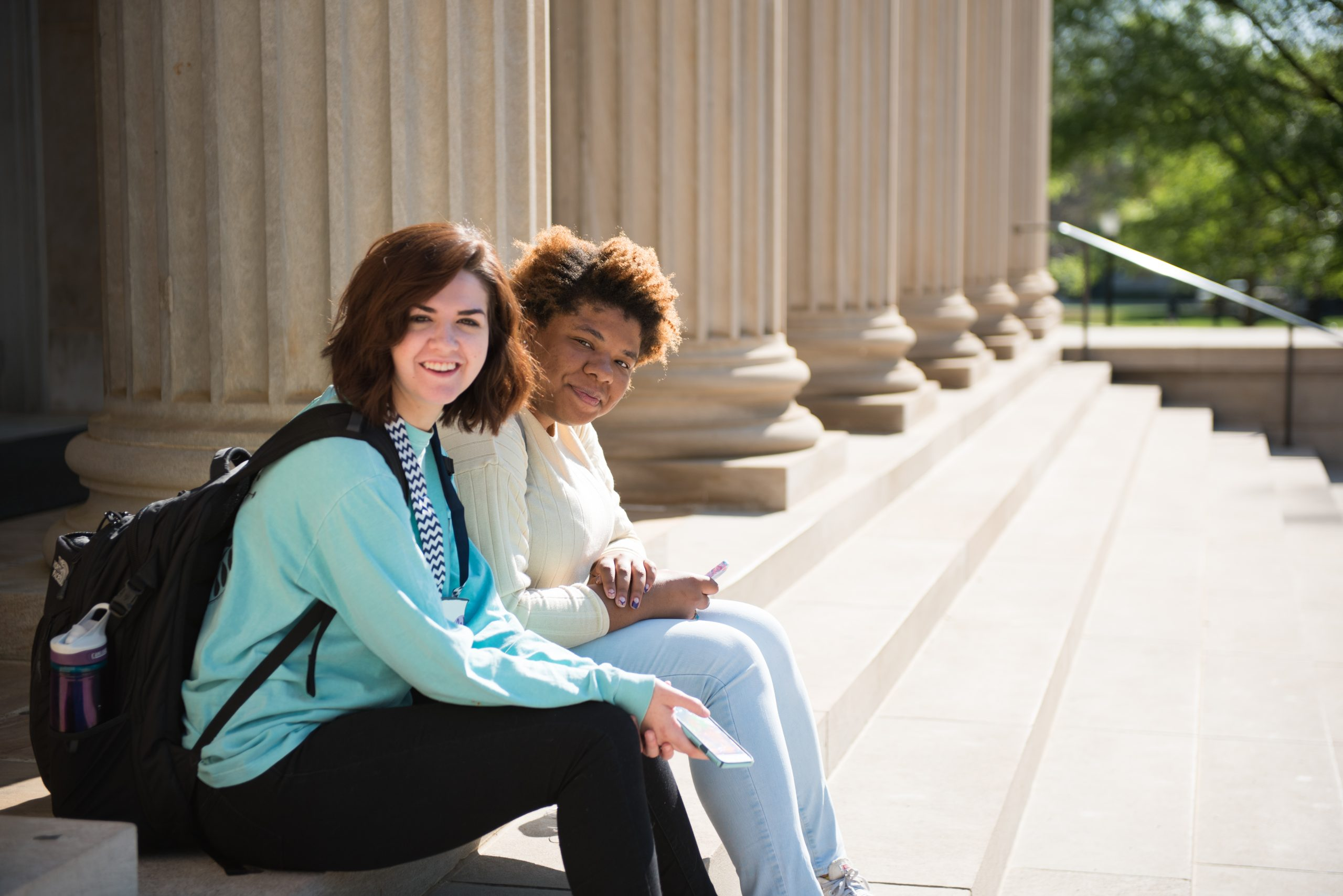 Two female students sit at the top of the Gorgas Library stairs