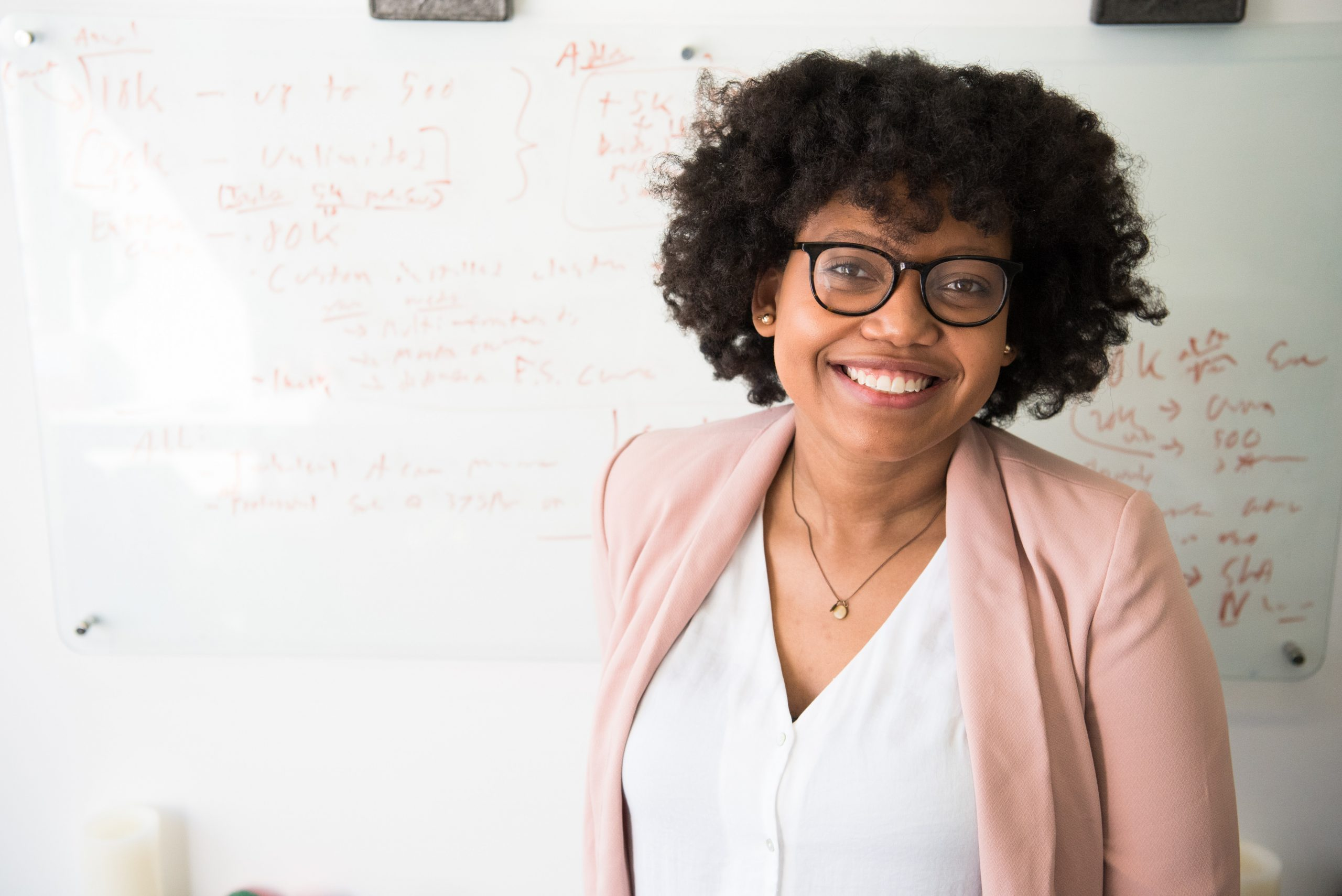Female, African-American Professor smiles in front of a whiteboard covered with mathematical notations