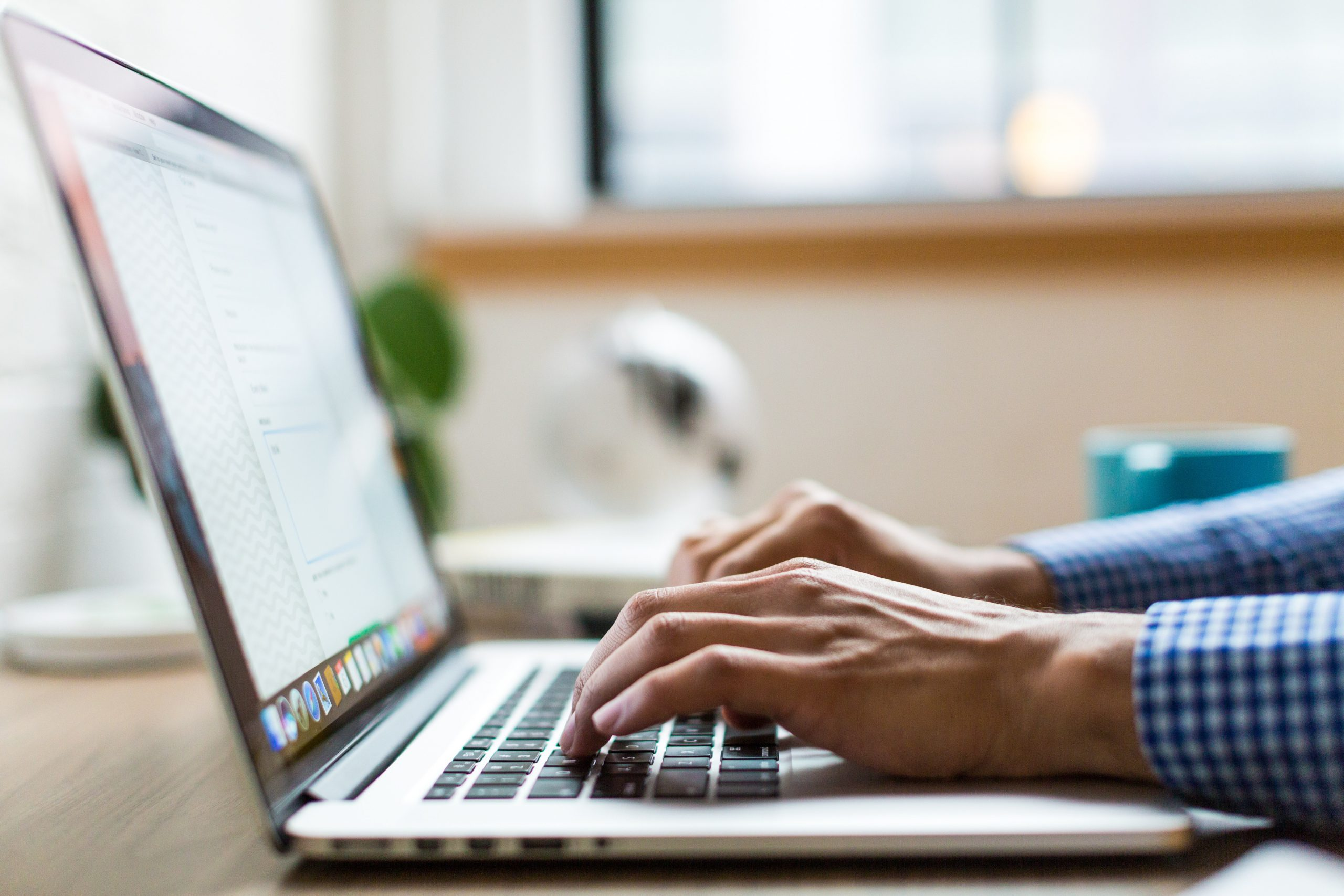 close up image of male hands typing on a laptop